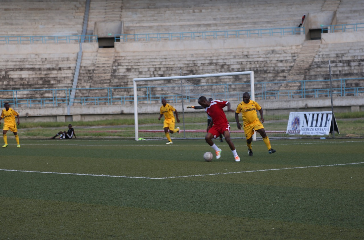 EALA Striker, Ibrahim Jamal shields the ball away from a defender of the Parliament of Tanzania