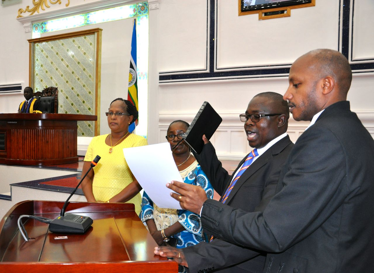 Hon Jean Marie Muhirwa takes the Oath administered by the EALA Senior Clerk Assistant, Stephen Mugume as Members, Hon Emerence Bucumi (centre) and Hon Judith Pareno (left) look on