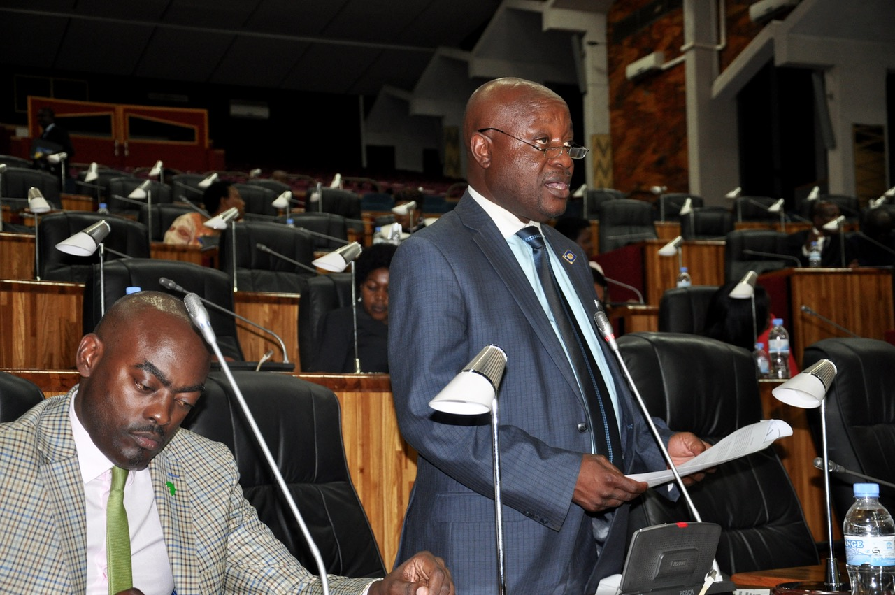 Hon Mike Sebalu presents the report of the Committee to the House as Hon Mukasa Mbidde pays attention to the proceedings