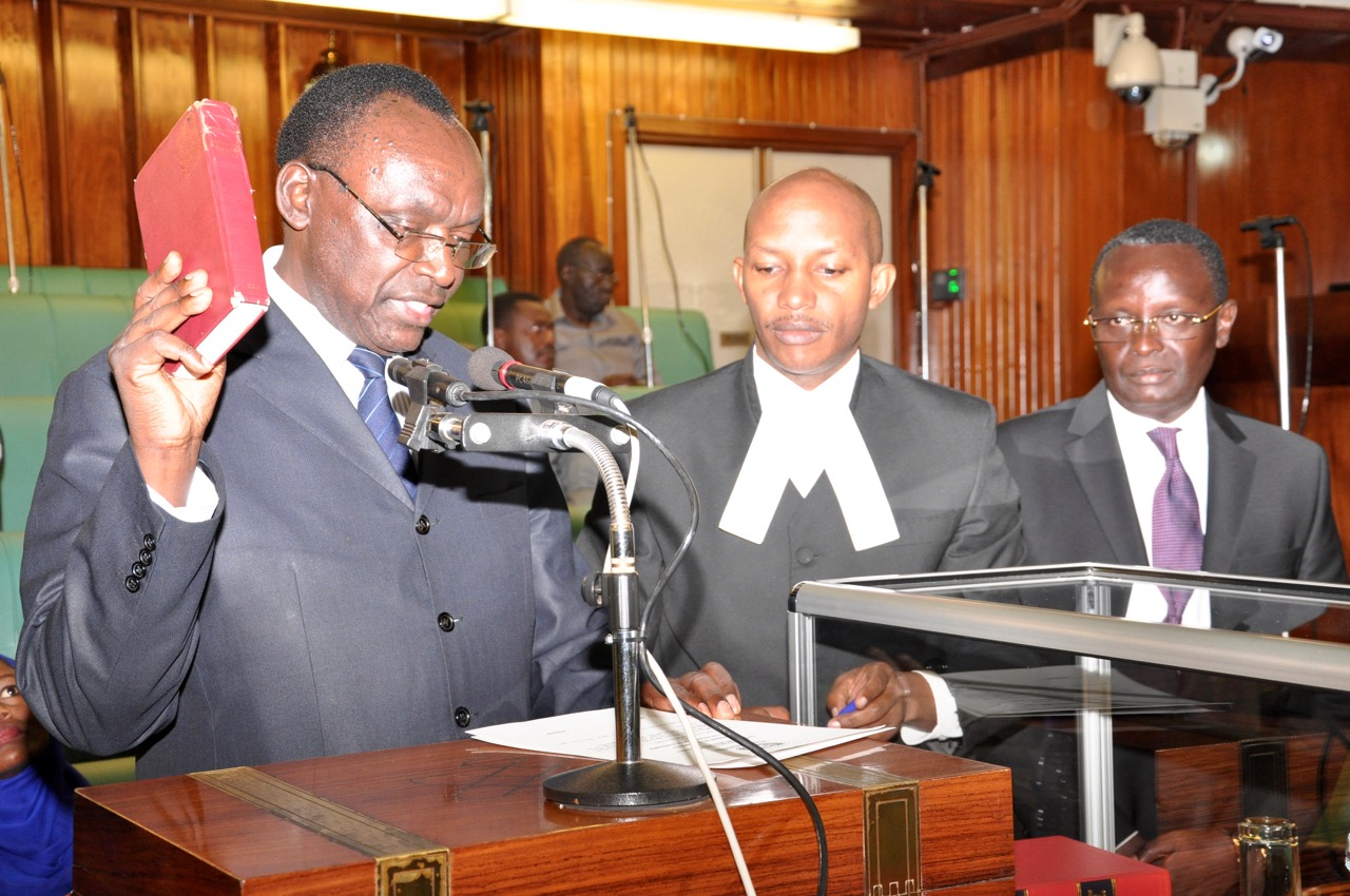 Hon Francois Kanimba, Minister for Trade, Industry and EAC takes the Oath, administered by Senior Clerk Assistant, Stephen Mugume as Hon Martin Ngoga looks on