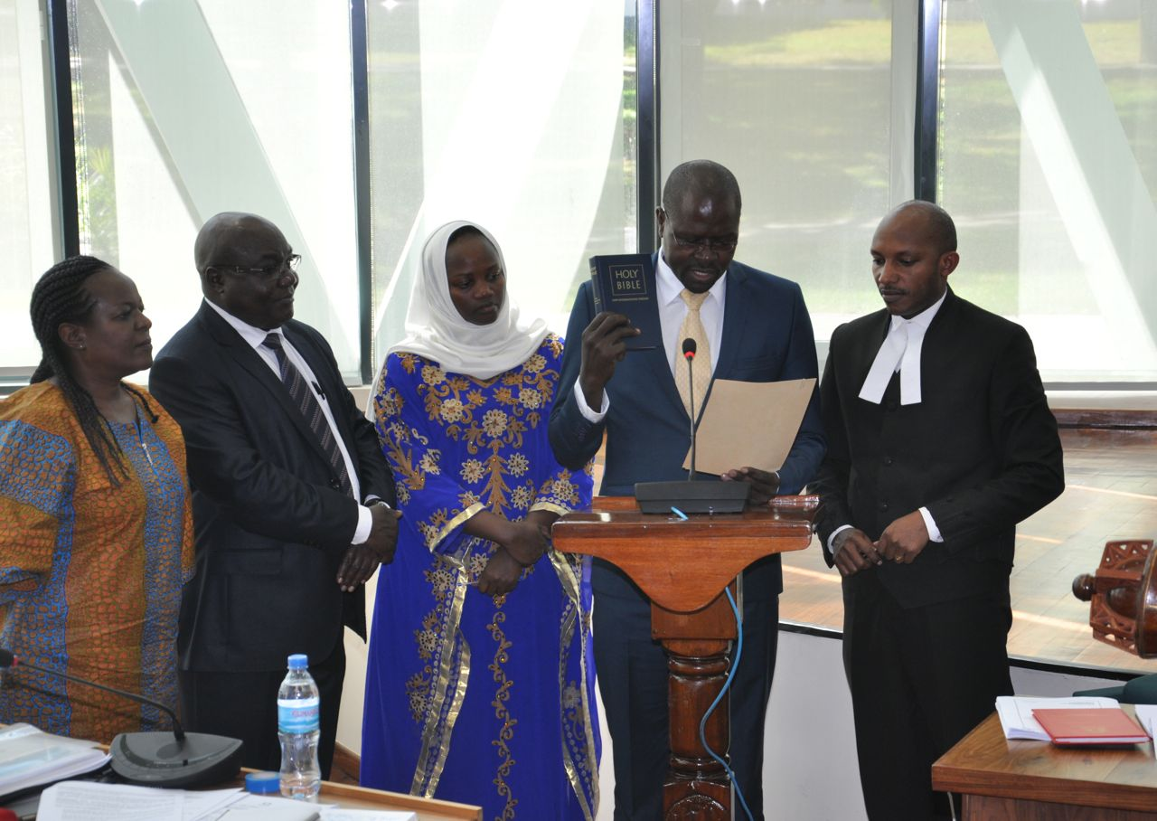 Hon Maganda Julius Wandera takes the oath of allegiance. Looking on from left is Hon Dora Byamukama, Hon Chris Opoka and Hon Nusura Tiperu.  On right is Senior Clerk Assistant, Stephen Mugume