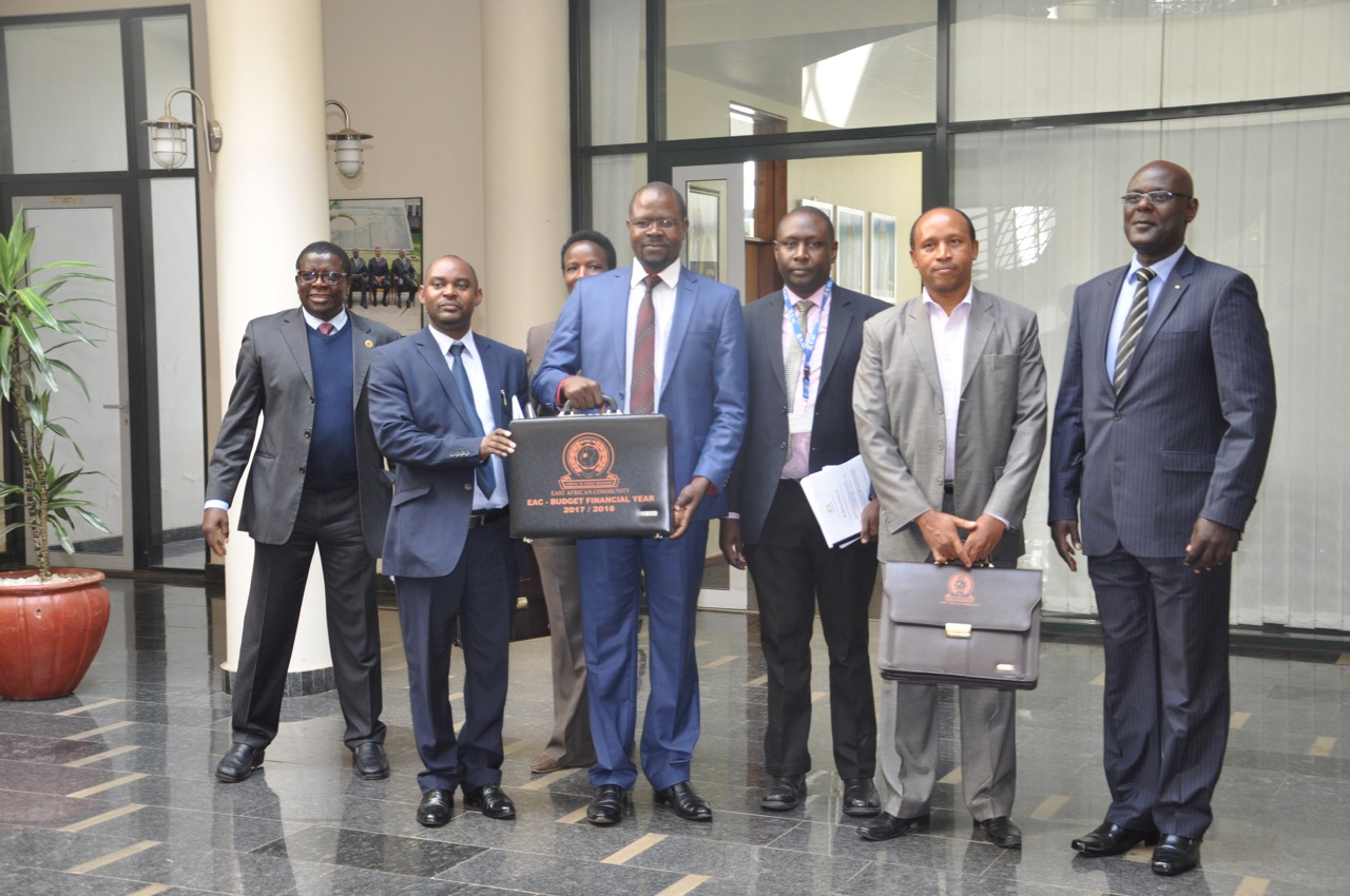 The Minister for State, EAC Affairs, Uganda, Hon Julius Maganda holds aloft the briefcase containing the EAC Budget Speech as other EAC Senior Officers look on