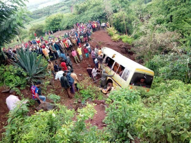 Residents gather at the scene of an accident that killed schoolchildren, teachers and a minibus driver at the Rhota village along the Arusha-Karatu highway in Tanzania's northern tourist region of Arusha, May 6, 2017.